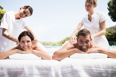 Young couple receiving a back massage from masseur Stock Image