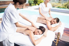 Young couple receiving a back massage from masseur Stock Photos