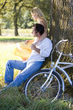 Young couple reclining against tree by bicycle, side view Stock Images