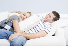 Young Couple Reclining on Sofa Royalty Free Stock Photography