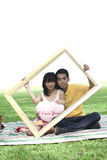 Young couple with rectangle frame Stock Images