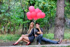 Young couple with red balloons on nature Royalty Free Stock Photography