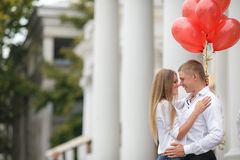 A young couple with red balloons on the street Royalty Free Stock Images