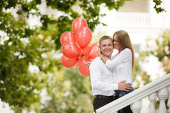 A young couple with red balloons on the street Royalty Free Stock Photos