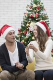 Young couple in red hat sitting on sofa between christmas trees stock photos