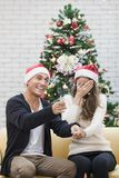 Young couple in red hat sitting on sofa between christmas trees royalty free stock image