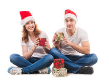Young couple in red hats hugging on the floor Stock Photos