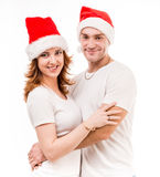 Young couple in red santa hats Stock Images