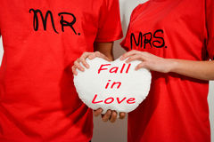 Young couple in red shirts holding white fabric heart with text. Fall in love Stock Photos