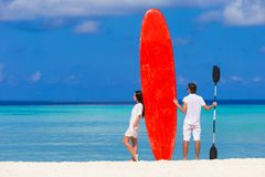 Young couple with red surfboard on white beach Royalty Free Stock Photos