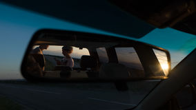 Young couple in reflection of auto mirror, look at map at sunset near road Stock Images