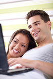 Young couple relax in bed with laptop Stock Images