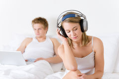 Young couple relax in bed with music and laptop Royalty Free Stock Photos