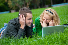 Young couple relax and listen to music. From lapop on the grass in the park Stock Images
