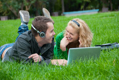 Young couple relax and listen to music. From lapop on the grass in the park Royalty Free Stock Photo