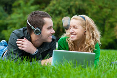 Young couple relax and listen to music. From lapop on the grass in the park Royalty Free Stock Photography