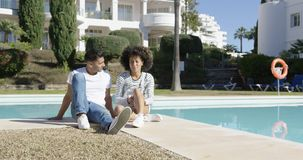Young couple relaxing alongside an urban pool stock video footage