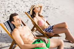 Young couple relaxing on armchair on the beach Royalty Free Stock Photos