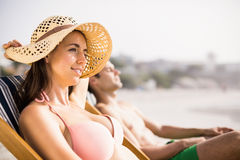 Young couple relaxing on armchair on the beach Royalty Free Stock Photo