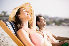 Young couple relaxing on armchair on the beach Stock Photo