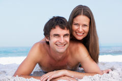 Young Couple Relaxing On Beach Wearing Swimwear. Smiling At Camera Stock Images