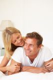 Young Couple Relaxing On Bed Royalty Free Stock Photo