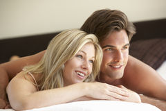 Young Couple Relaxing On Bed Royalty Free Stock Photos