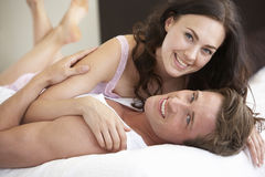 Young Couple Relaxing On Bed Stock Photography