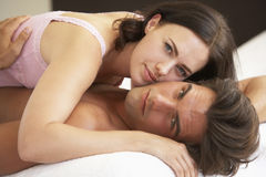Young Couple Relaxing On Bed Stock Photos