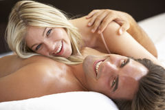Young Couple Relaxing On Bed Stock Images