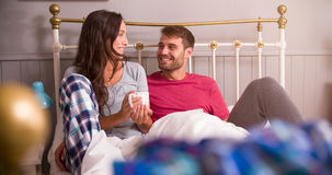 Young Couple Relaxing In Bed With Hot Drink Stock Images