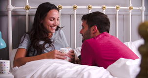 Young Couple Relaxing In Bed With Hot Drink. Young couple in bed together chatting and drinking coffee.Shot on Sony FS700 at frame rate of 25fps stock video footage