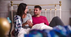 Young Couple Relaxing In Bed With Hot Drink. Young couple in bed together chatting and drinking coffee.Shot on Sony FS700 at frame rate of 25fps stock footage