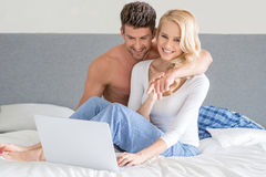 Young couple relaxing in bed using a laptop Royalty Free Stock Images