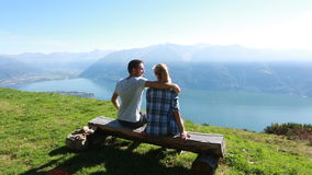 Young couple relaxing on bench, scenic view stock video footage