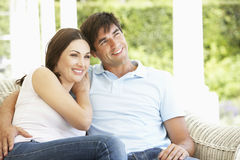 Young Couple Relaxing On Cane Sofa At Home Royalty Free Stock Photos