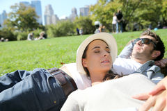 Young couple relaxing in central park lying in grass Stock Photo