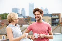 Young Couple Relaxing With Coffee On Roof Terrace Royalty Free Stock Photos