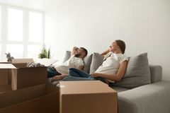 Young couple relaxing on couch just moved into new home. With cardboard boxes, men and women sitting on sofa with belongings in living room ready to move Stock Images