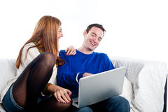 Young couple relaxing on the couch with laptop Stock Photos