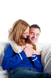 Young couple relaxing and cuddling together on the sofa Royalty Free Stock Photos