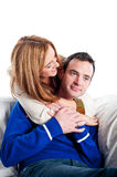 Young couple relaxing and cuddling together on the sofa Royalty Free Stock Image