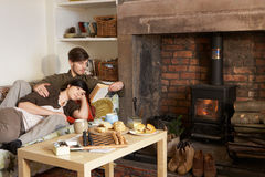 Young couple relaxing by fire Stock Images