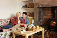 Young couple relaxing by fire Royalty Free Stock Photos