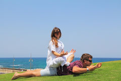 Young couple relaxing on the grass. A lovely summer day, the family is happy. Young couple relaxing on the grass by the sea. Charming young women is pregnant Royalty Free Stock Photography