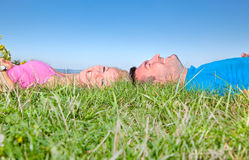 Young couple relaxing on grass in park Stock Photos