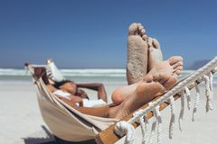 Young couple relaxing on hammock at beach stock photos