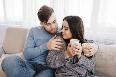 Young couple relaxing at home with hot drinks royalty free stock photos