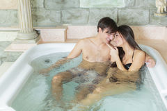 Young couple relaxing in hot tub Stock Photography