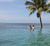 Young couple relaxing in infinity pool under coco palms Stock Images